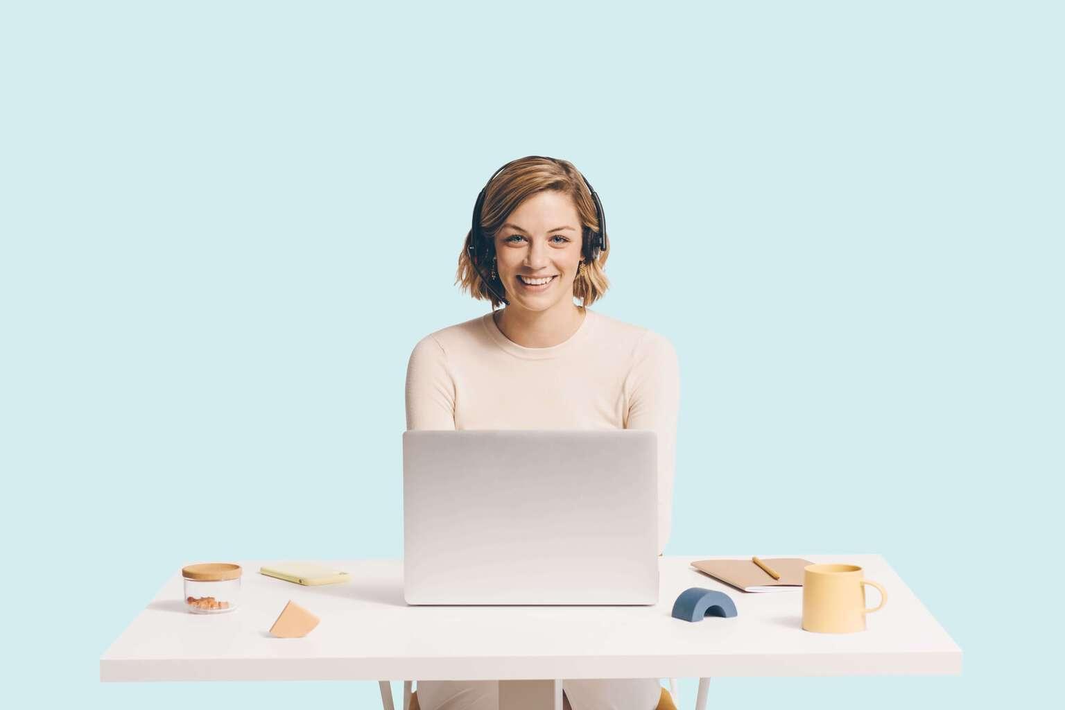 Agent d'assistance portant un casque, assis derrière un bureau avec un ordinateur portable et divers objets posés sur le bureau.