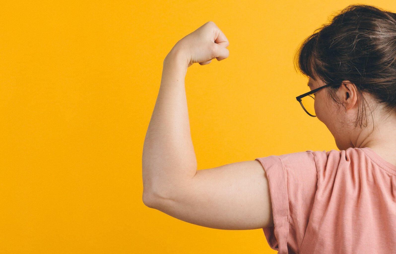 Personne tenant son bras et fléchissant son biceps pour montrer sa force
