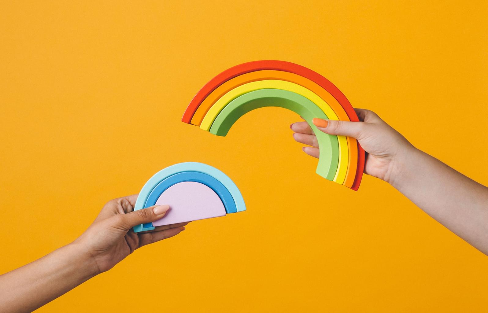 image of hands and rainbows on bright background