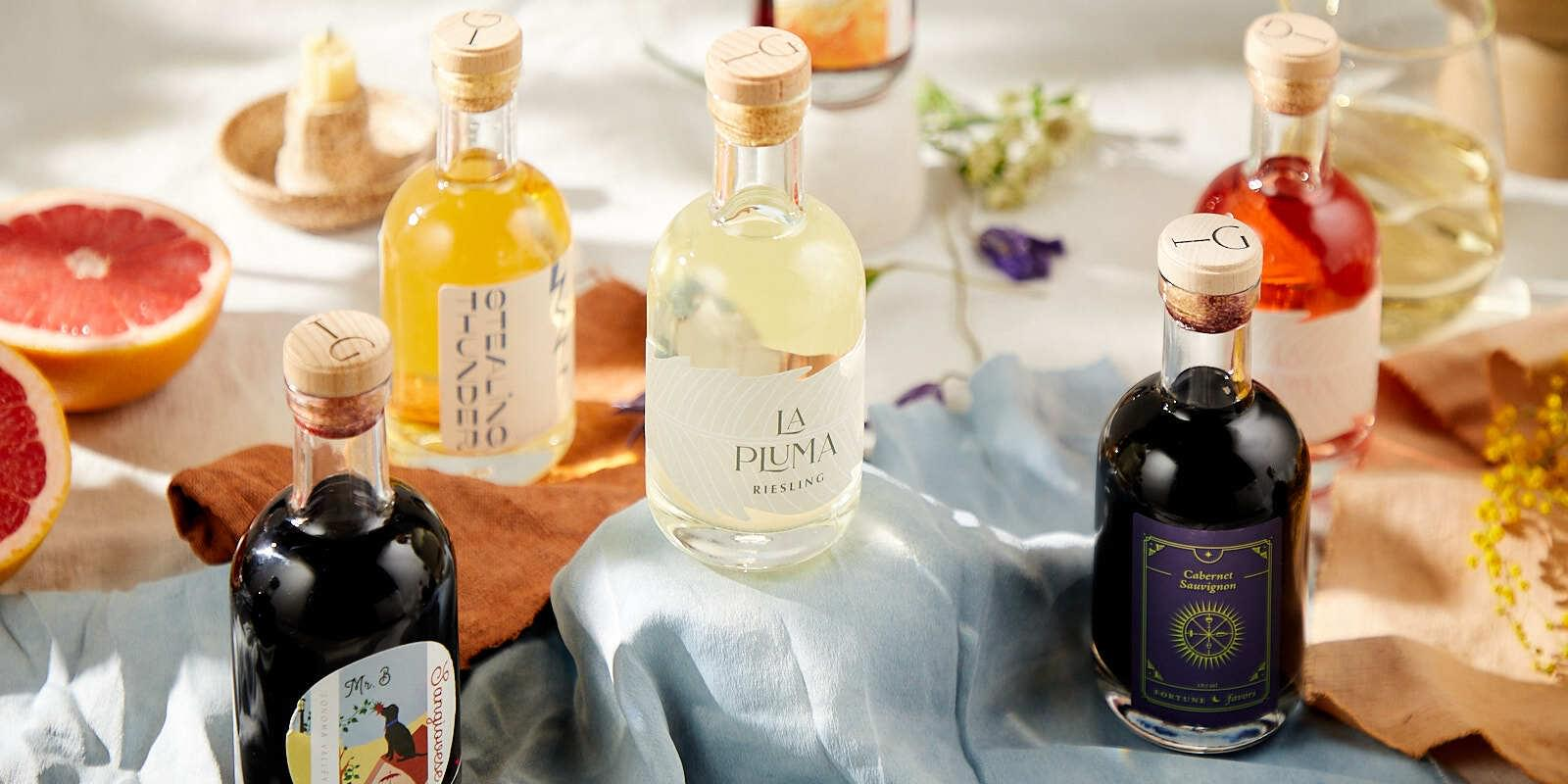 Bottles of wine from In Good Taste displayed casually on a table with various fruit, flowers, and candles surrounding them