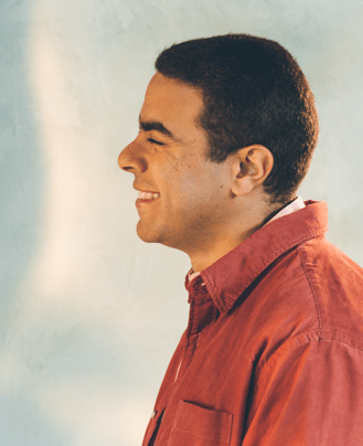 Photo: Portrait of young man smiling, wearing a red button-up shirt.